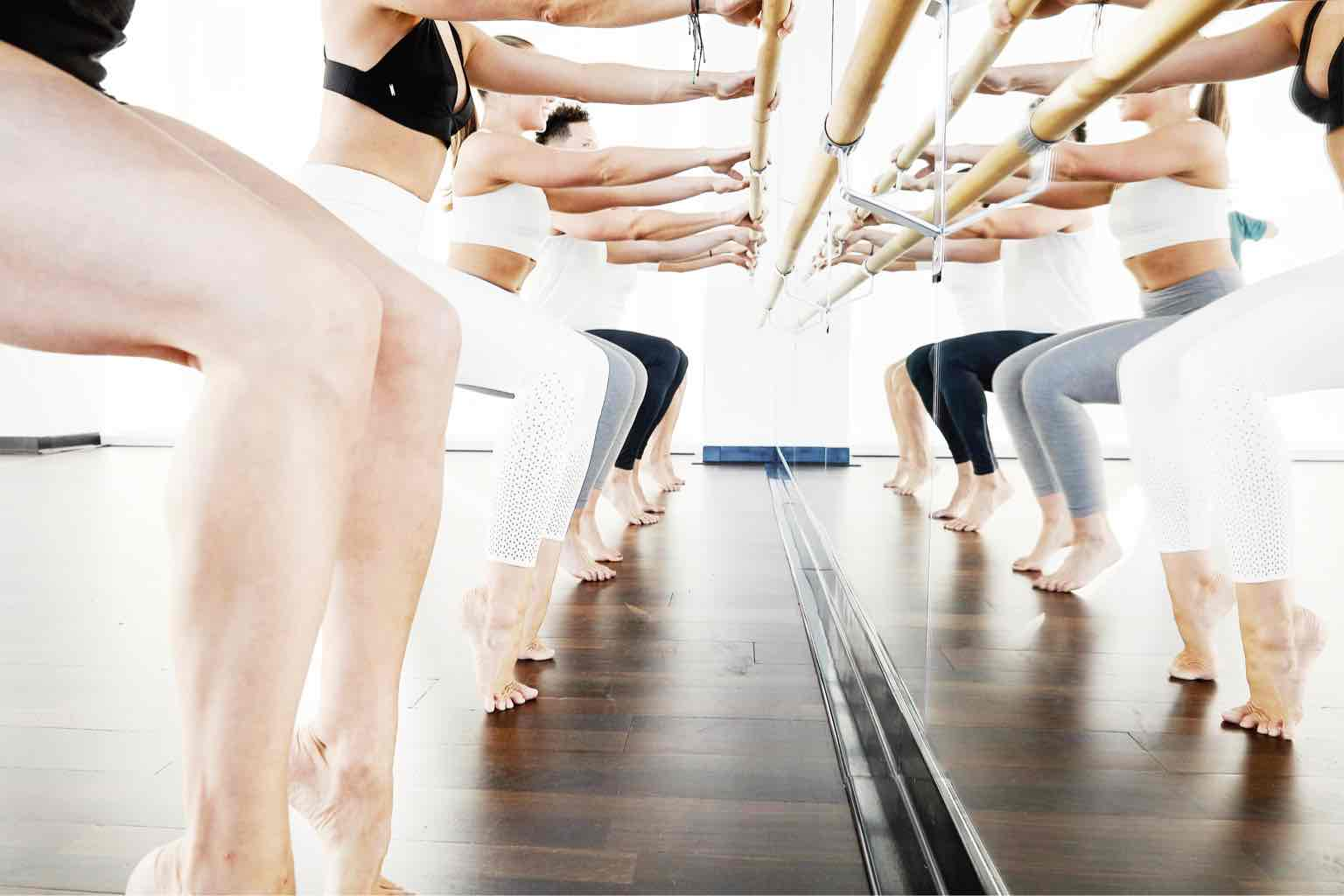 Five women in a row standing on their toes in a sitting position while holding onto a barre attached to a mirrored wall