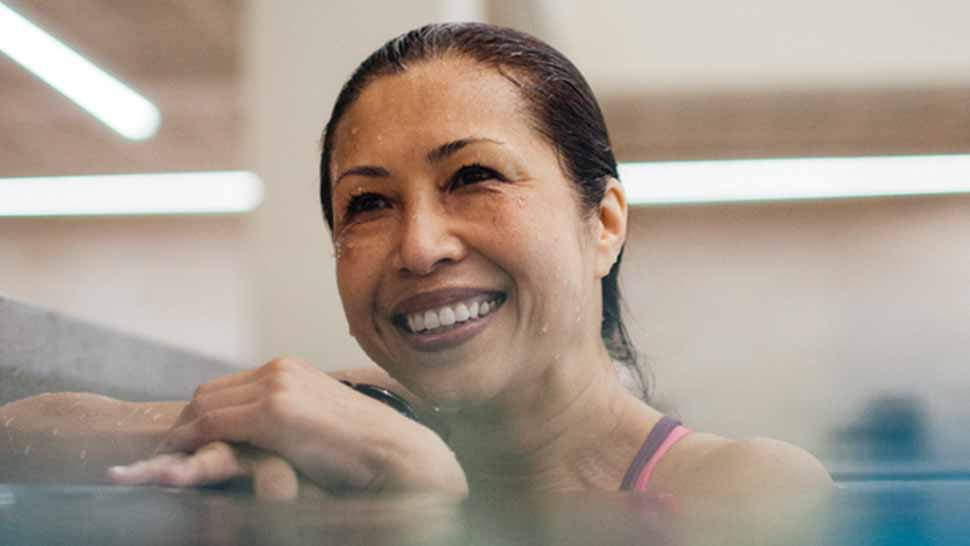 smiling woman at the edge of a pool