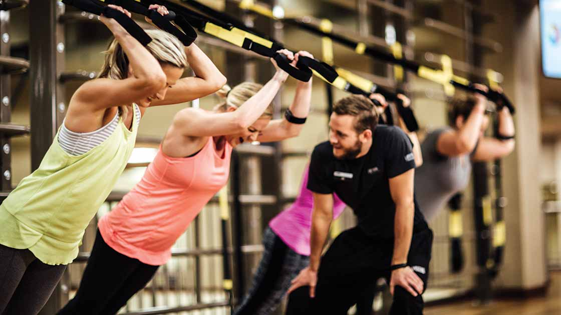 women in strength training with a male trainer
