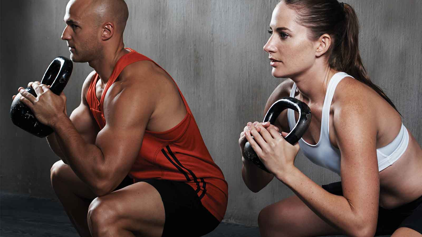 a man and a woman in a deep kettlebell squat