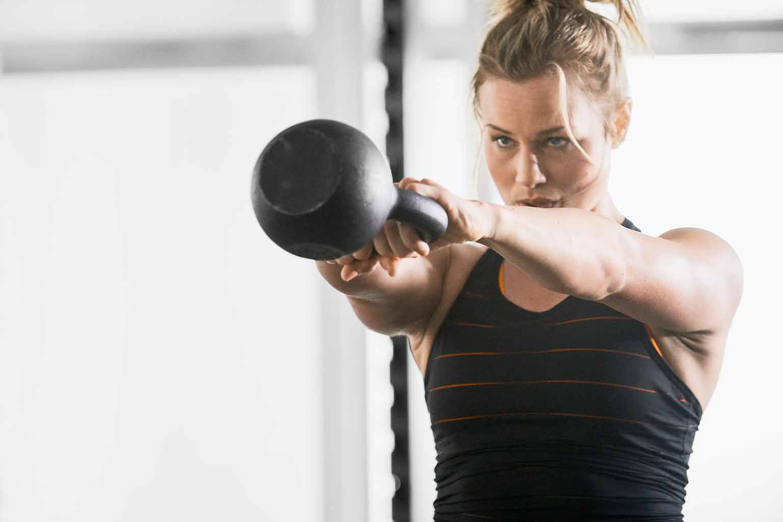 A woman in a black tank top with orange stripes holds a kettlebell in the up position of a kettlebell swing