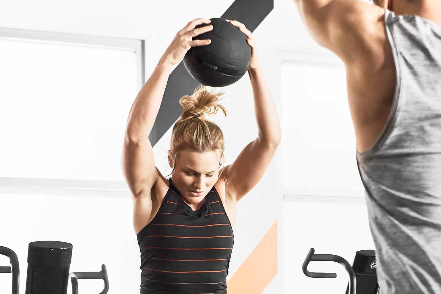 A woman in a black tank top with orange stripes holds a medicine ball over her head as she prepares to slam the ball to the ground