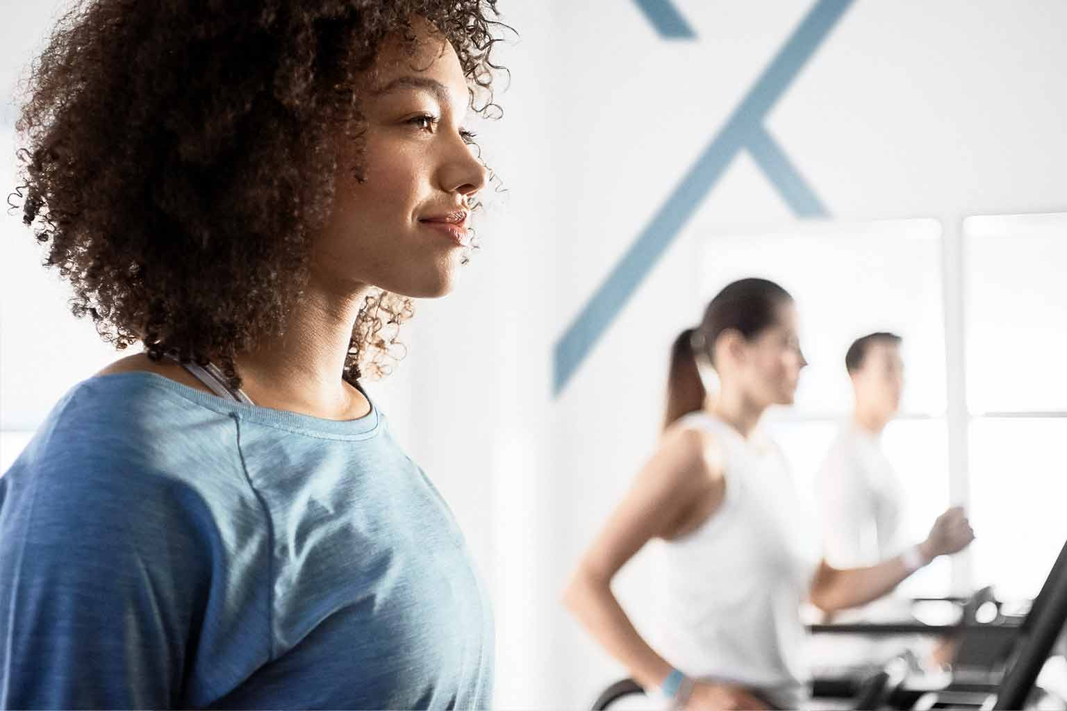 A woman in a blue workout shirt and one man and one woman in white workout clothes walk on treadmills