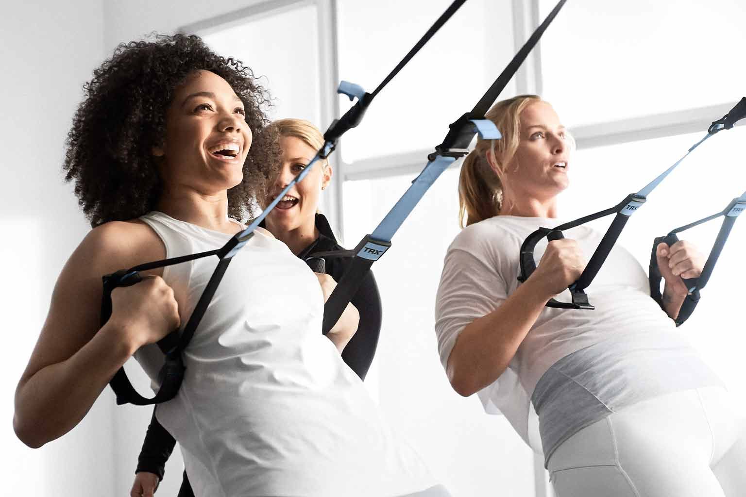 Two women in white workout clothes are cheered on by a GTX Burn coach as they do inverted ring rows