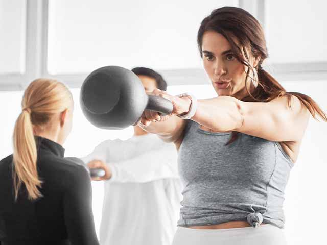 A woman in a gray tank top holds a kettlebell in the up position of a kettlebell swing as a GTX Cut coach gives instructions to two other class participants