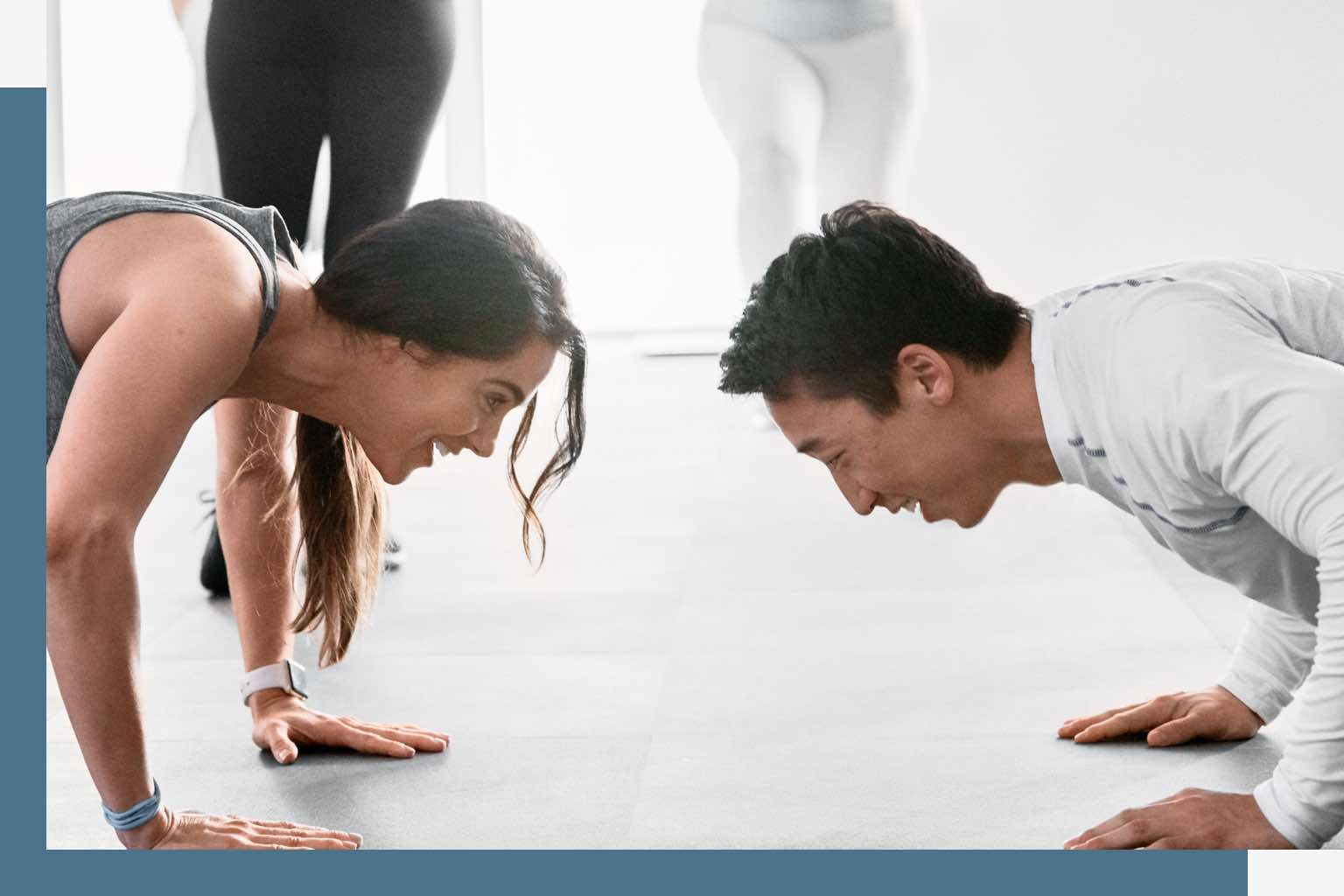 A woman in gray tank top and a man in a long-sleeved white workout shirt face each other while holding the push-up position