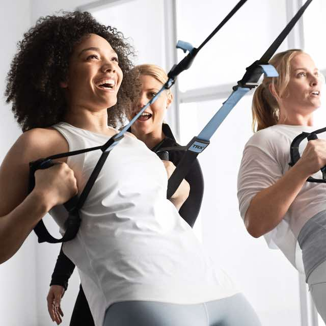 Two women working out with TRX bands in a group training class