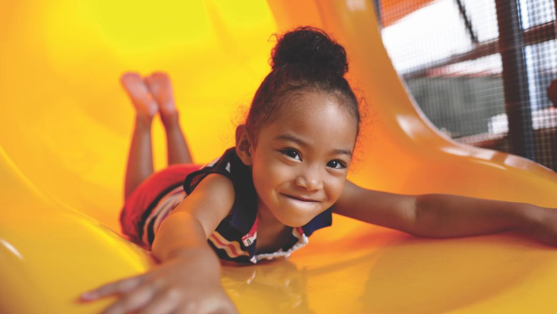 Child playing on a slide at the Life Time Kids Academy