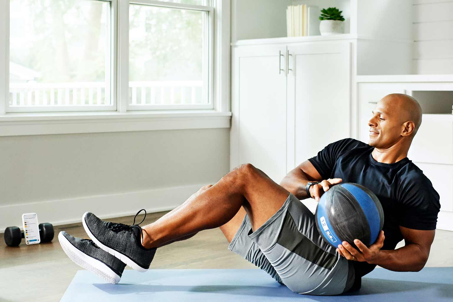 A man working out in his home with at home workouts from Life Time