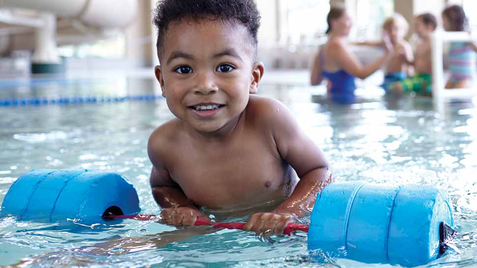 smiling baby in a swimming class