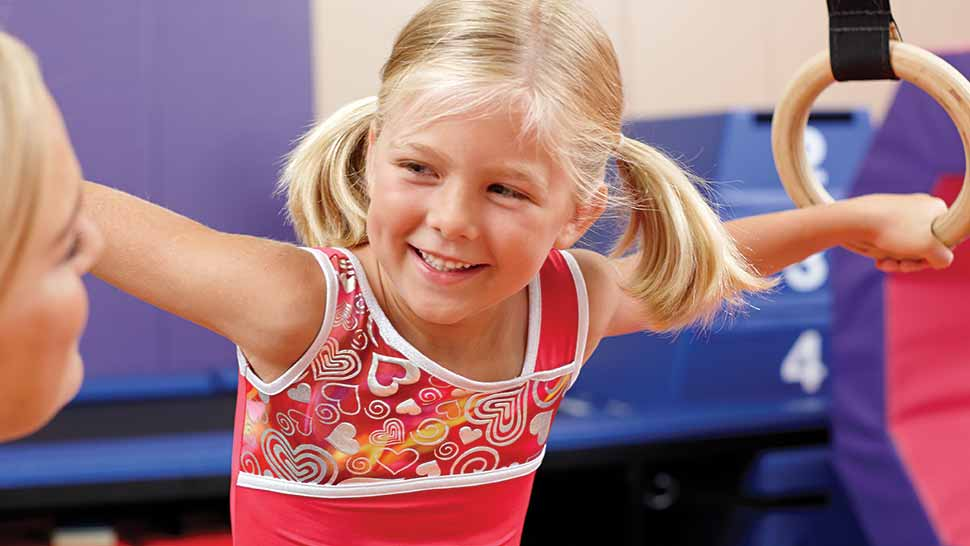 a happy girl learning kids' fitness from a teacher