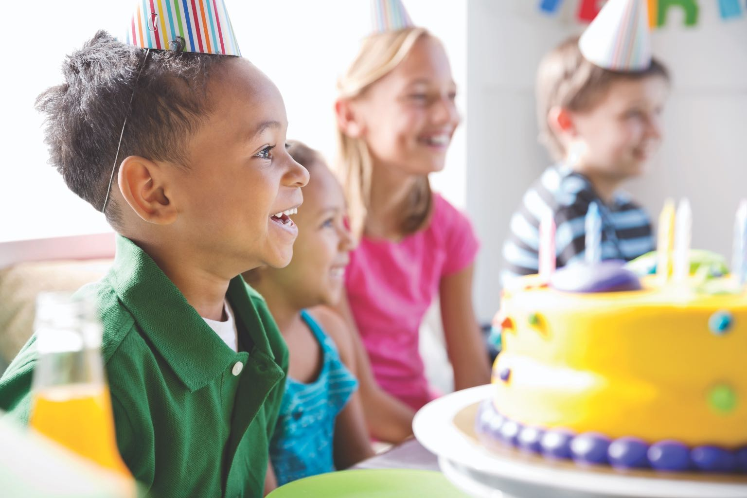 a group of kids sitting around a birthday cake