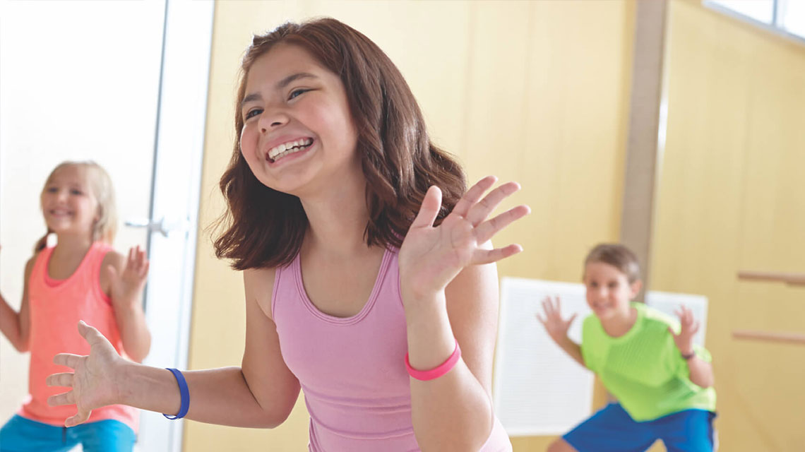Smiling kids exercising in gym