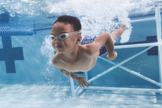 Boy swimming underwater in pool next to training platform