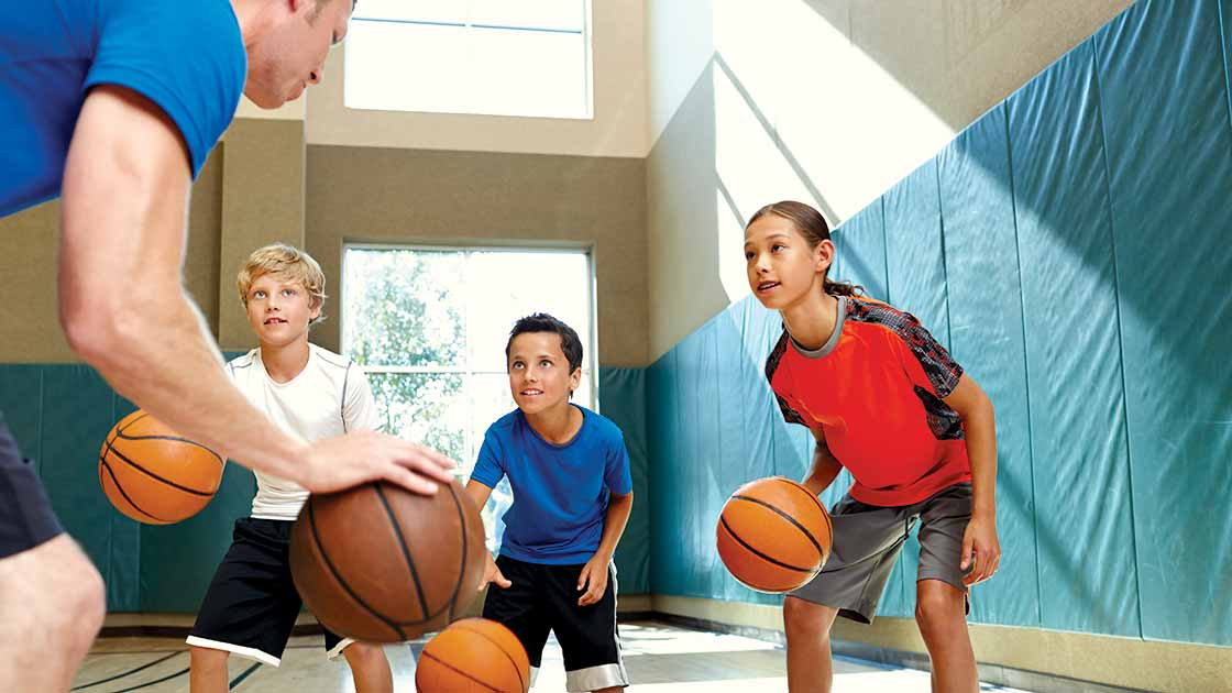 image of kids learning basketball from a teacher
