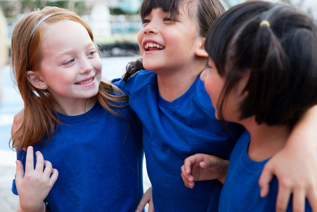 Three young girls, arm-in-arm, smiling and happy wearing blue camp t-shirts