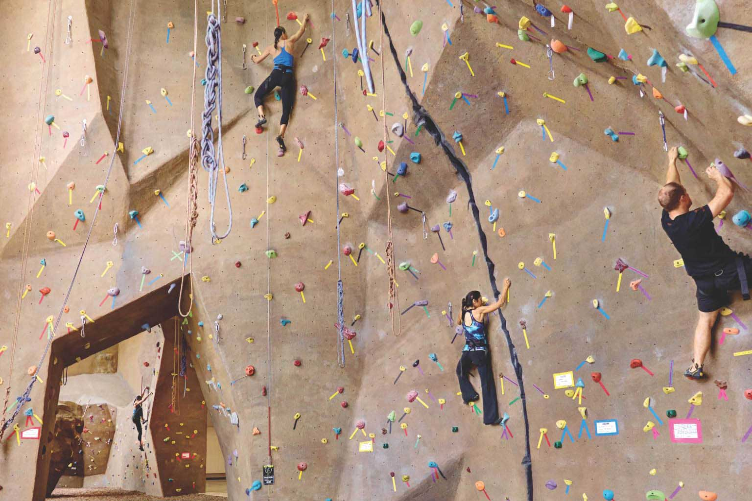 Three climbers at various heights, safely climbing the rock wall using ropes