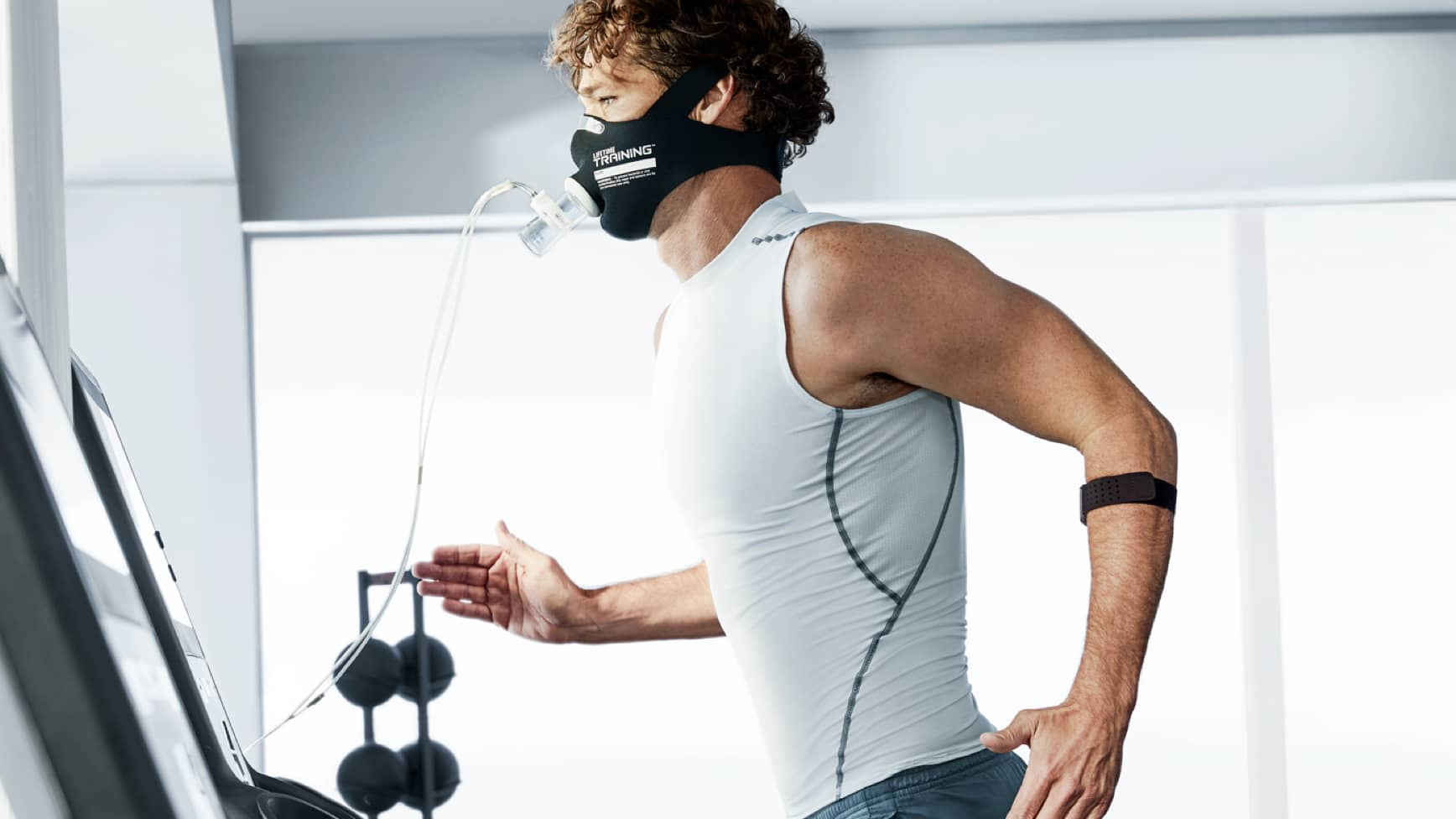 A Life Time member wearing a face mask and heart rate monitor runs on a treadmill