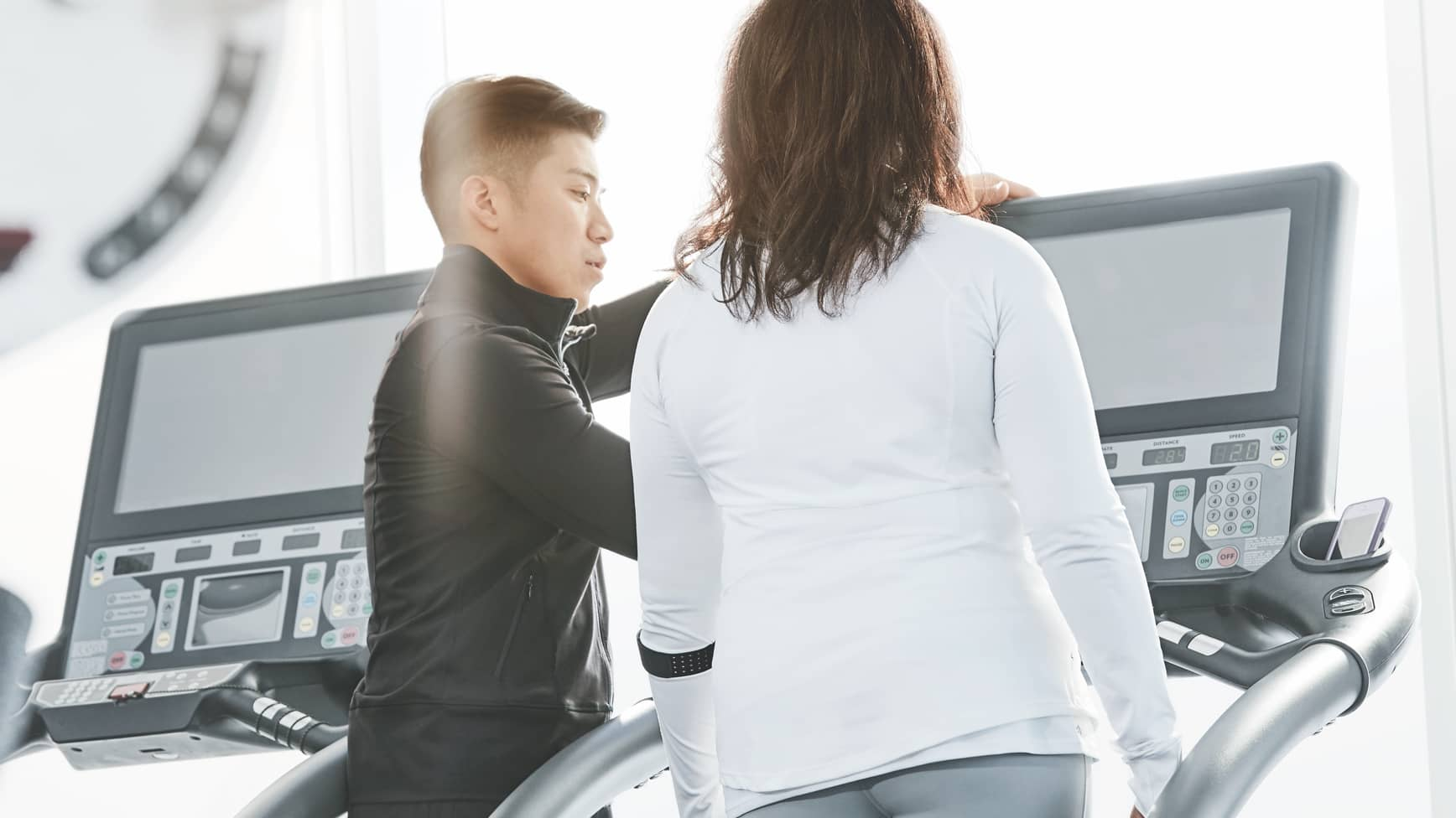 A trainer consults with his client, who is standing on a treadmill