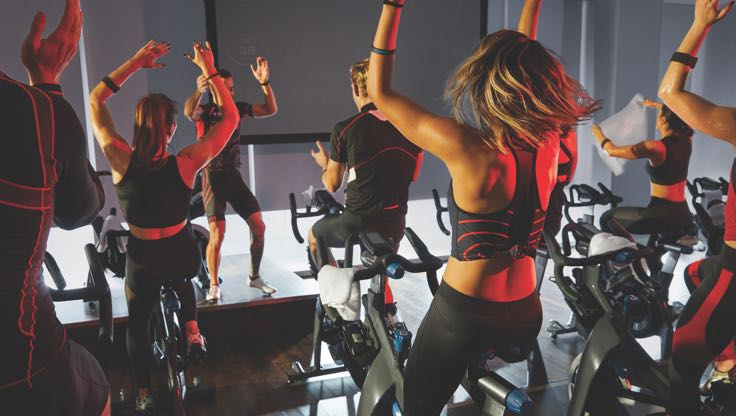 A group of people in Life Time's indoor cycle studio