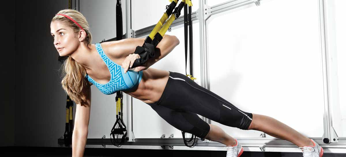 A woman using one of Life Time's TRX suspensions