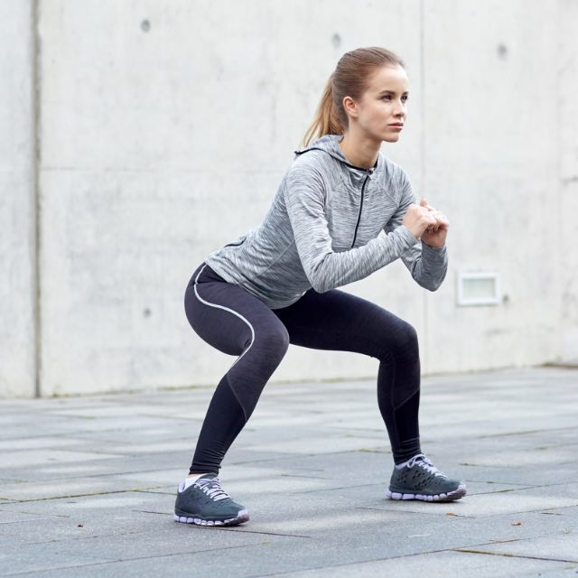 Woman doing a squat with only bodyweight.