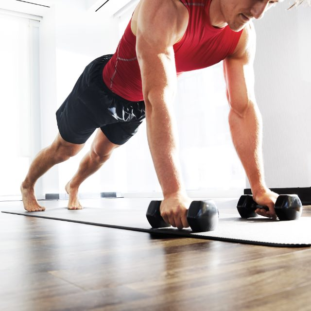 Two people in push up position with dumbbells.
