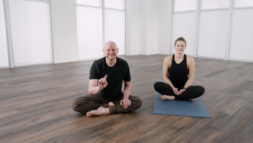 Two people in a seated yoga position