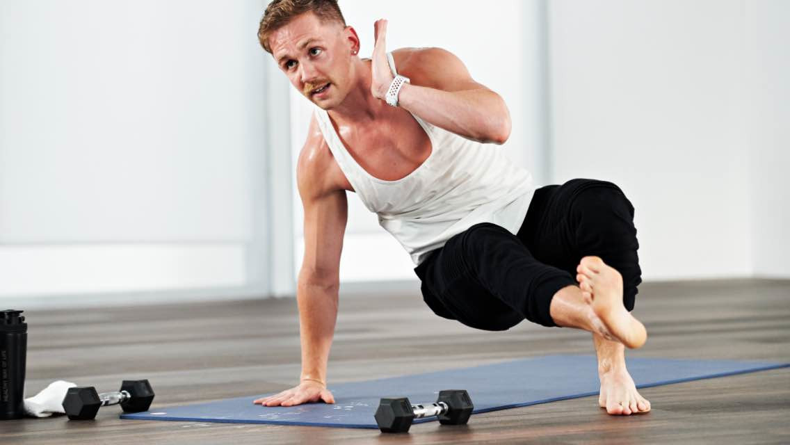 Man doing an at home yoga workout with Life Time Classes on demand