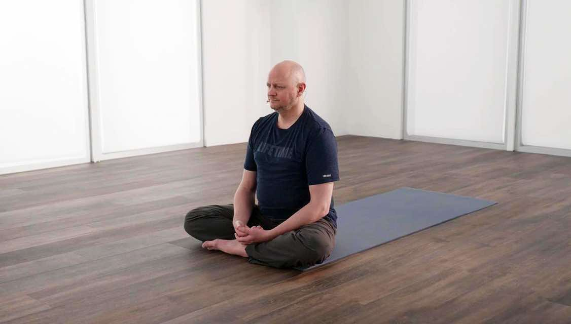 Man in a seated yoga pose