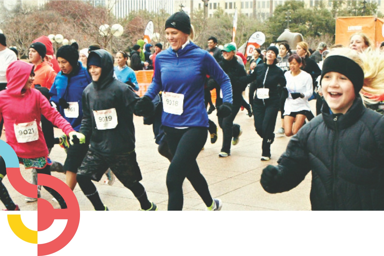 Crowd of people wearing winter gear running outside at a 5K race