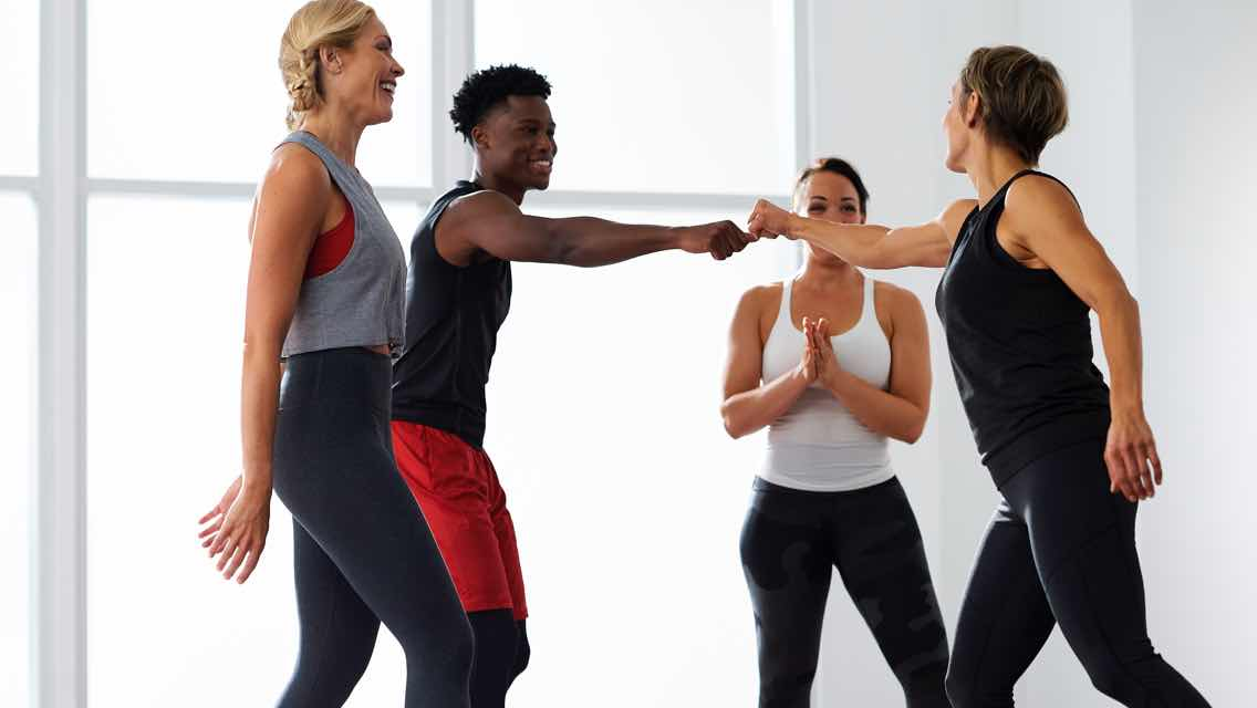 Four people cheering each other on in a group fitness class at Life Time