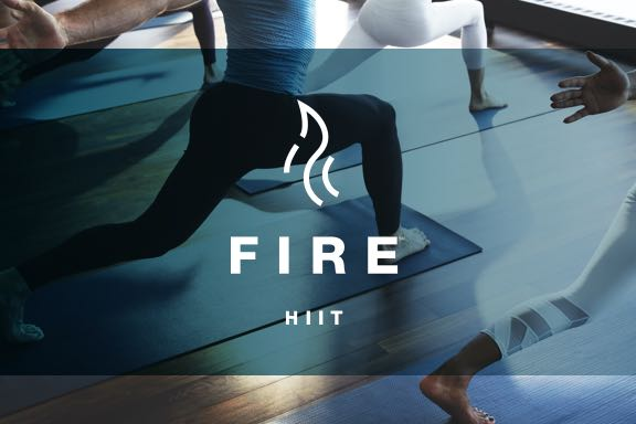 a group of people in a fire HIIT yoga class