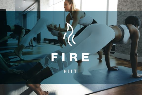 a group of women in a fire HIIT yoga class