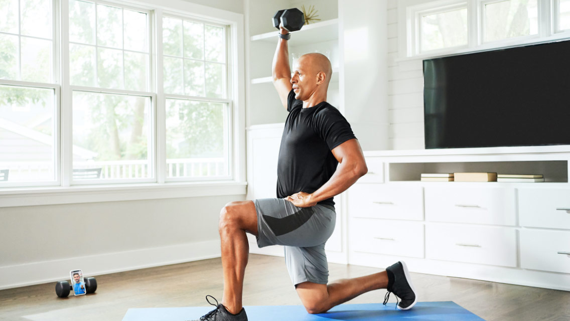 Man following directions from his trainer on his cell phone during an at-home virtual training workout session
