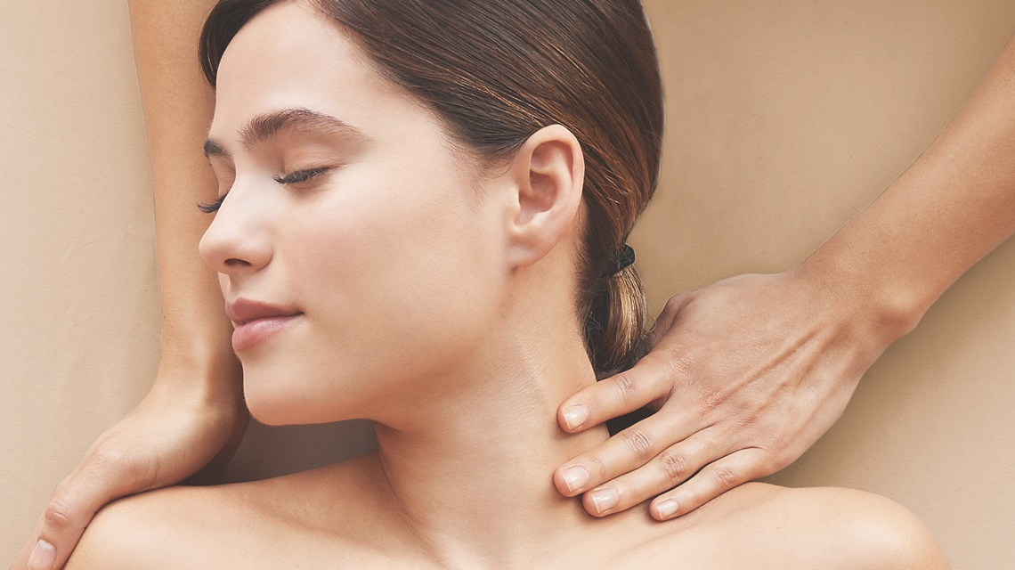 Woman's face relaxed with eyes closed receiving a neck massage