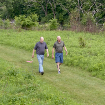 An image of Scott Morton and his friend walking on a grassy path