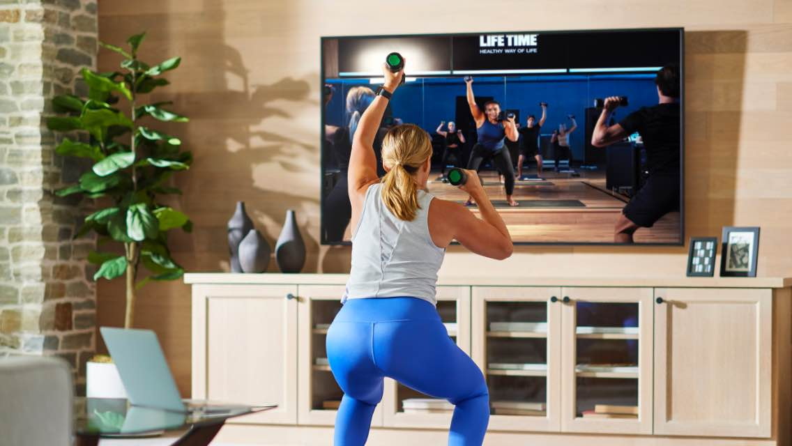 A woman works out in her living room, mirroring the trainer-led move being displayed on her large tv