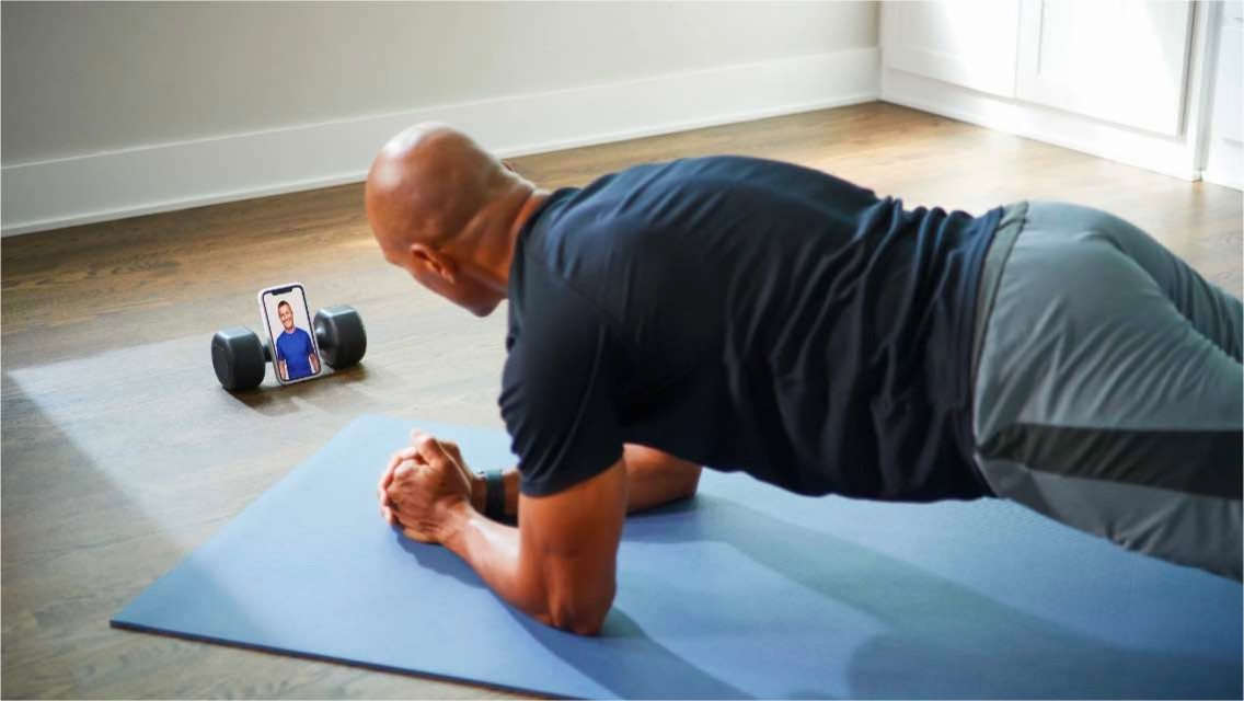 A man holds a plank, while an instructor coaches him on his cell phone