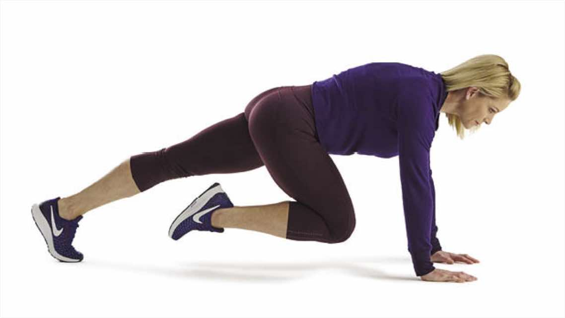 Woman wearing athletic clothing doing mountain climbers