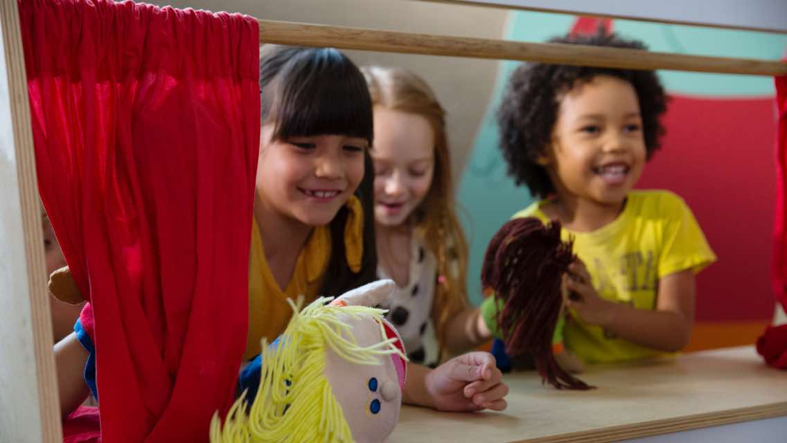 Three children putting on a puppet show in an indoor playroom