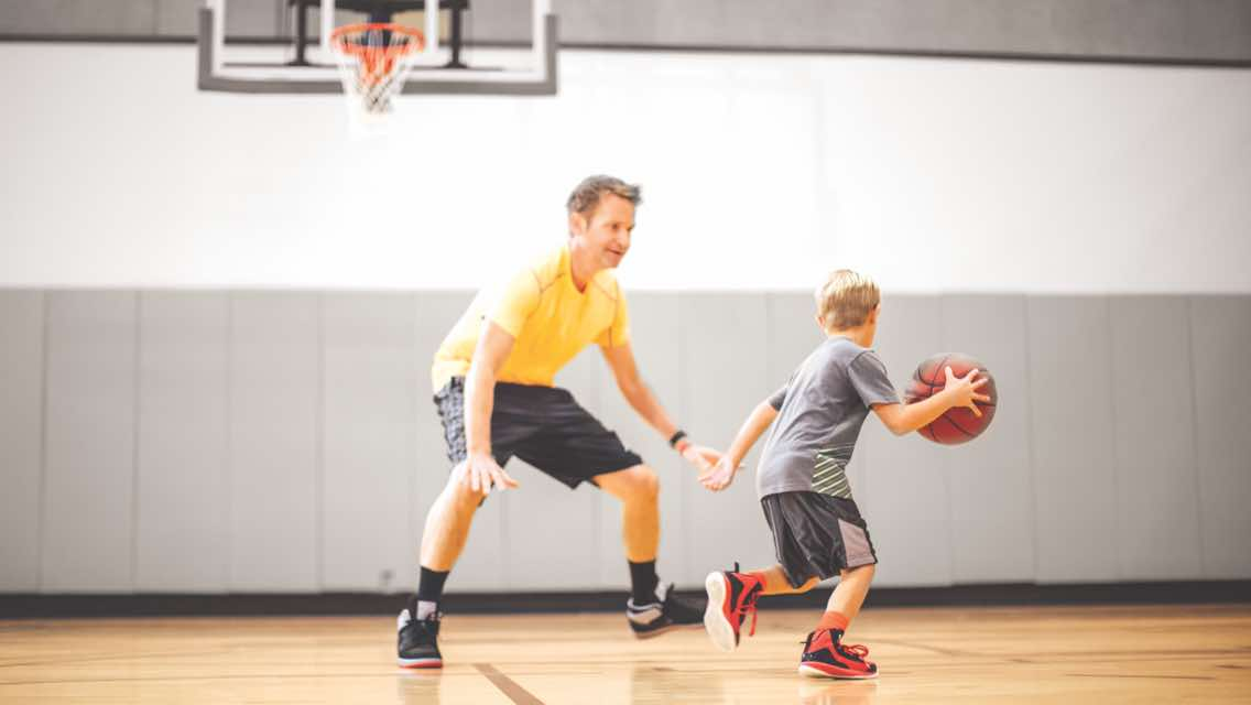A man and male child playing one-on-one basketball in a Life Time gym