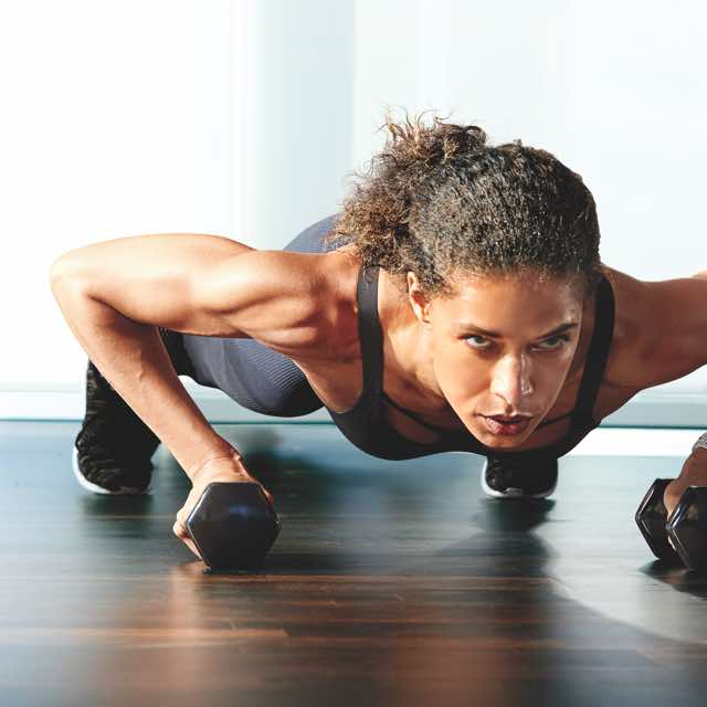 Woman in athletic clothing holding a plank position with a dumbbell in each hand