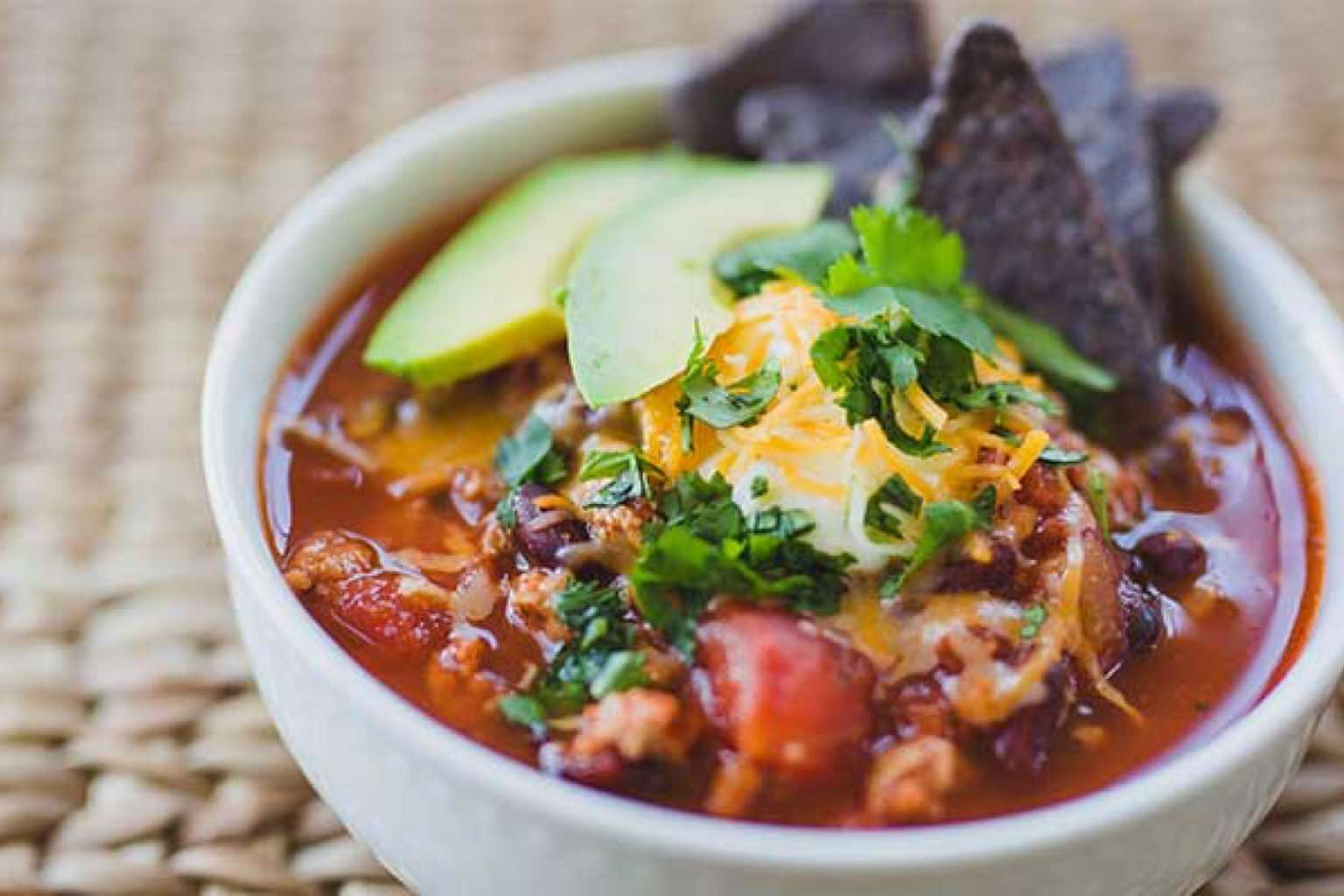 Close view of a bowl of chili topped with avocado, tortilla chips, shredded cheese and cilantro