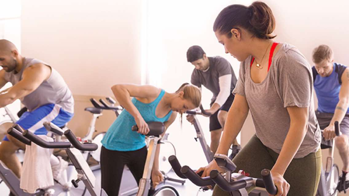 Five people setting up their bikes and preparing for an indoor cycle class