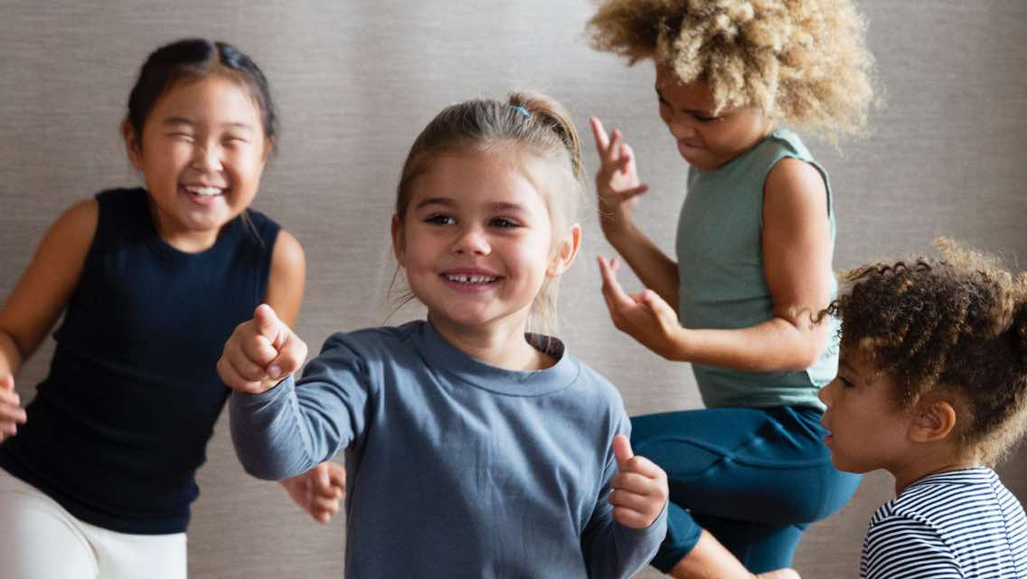 Four children dancing together in a brightly lit yoga studio