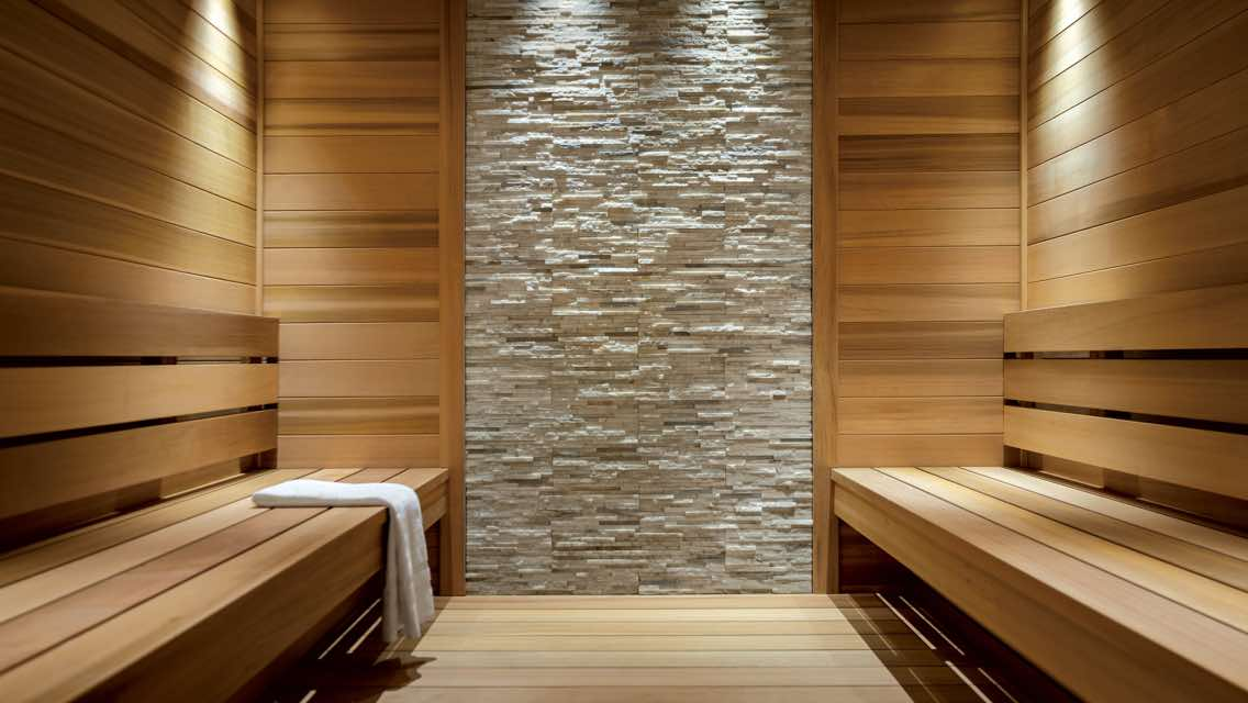 A wood paneled sauna with stone tiling and a white towel laid out on the wood bench