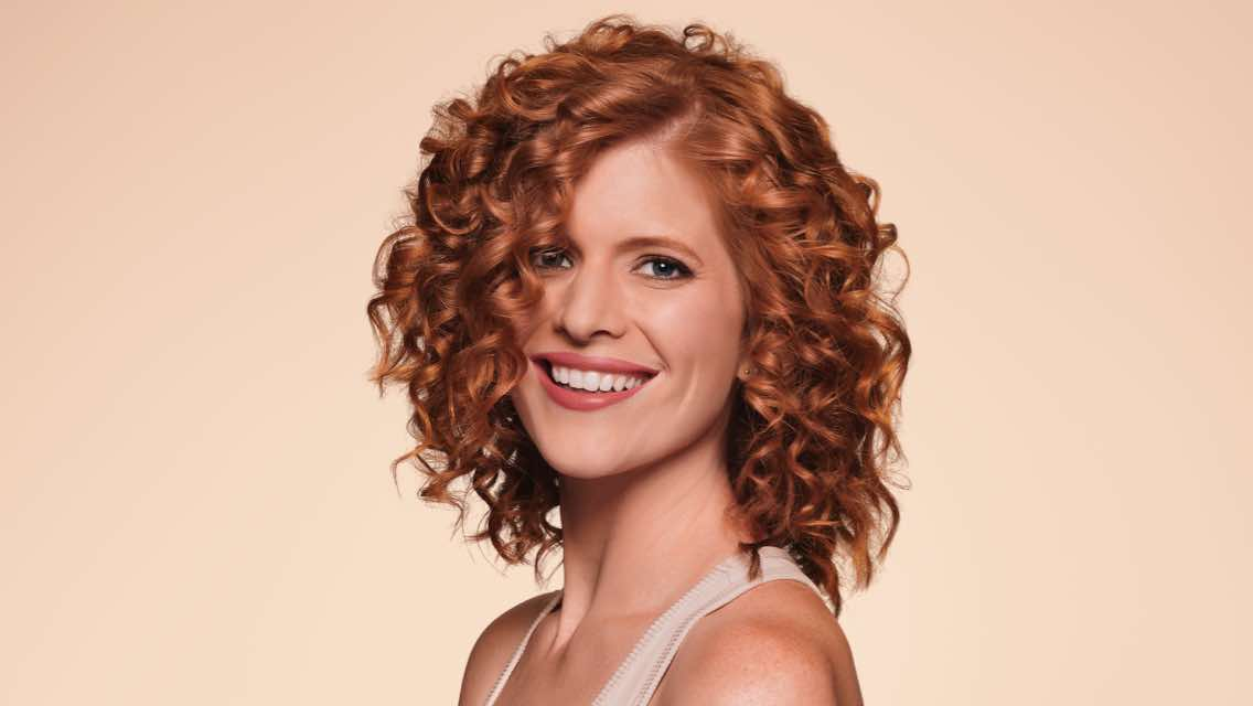 Close view of smiling woman with shiny, red curly hair done at the LifeSpa