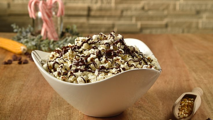 a bowl of popcorn with chocolate drizzle sitting on a wood table