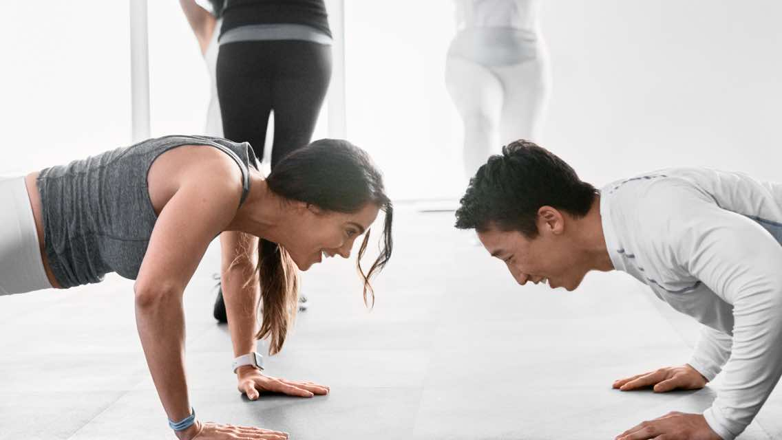 A man and woman facing each other while doing push-ups on the floor of a fitness studio